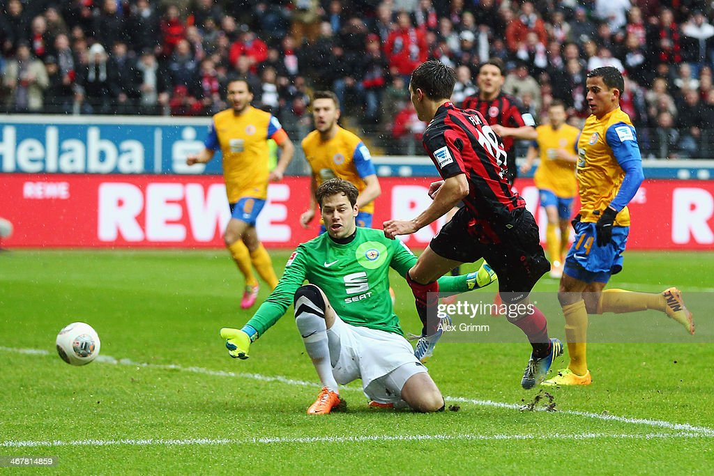 Johannes Flum of Frankfurt scores his team's first goal against goalkeeper Daniel Davari of Braunschweig during the Bundesliga match between...