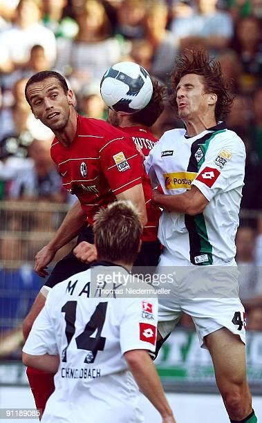 Johannes Flum of Freiburg jumps for a header with Karim Matmour of M'gladbach during the Bundesliga match between SC Freiburg and Borussia M'gladbach...