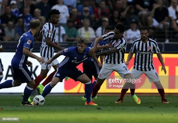 Johannes Geis of Schalke and Max Meyer of Schalke and Omar Mascarell of Frankfurt Szabolcs Huszti of Frankfurt battle for the ball during the...