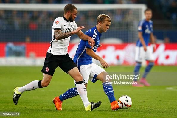 Johannes Geis of Schalke battles for the ball with Luc Castaignos of Eintracht Frankfurt during the Bundesliga match between FC Schalke 04 and...