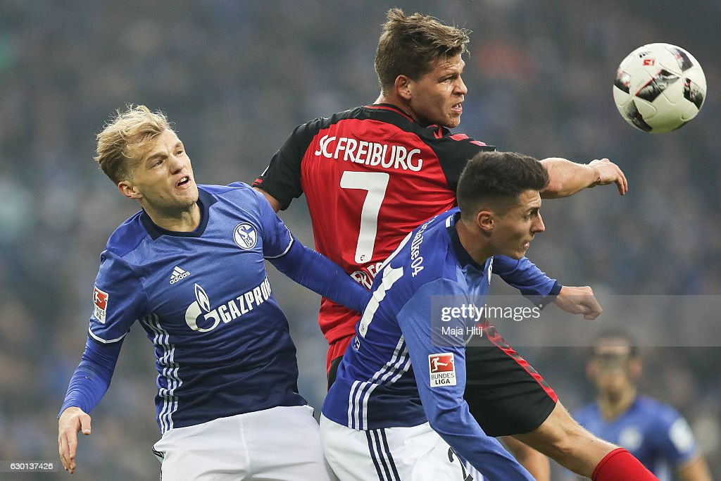 Johannes Geis of Schalke (L-R), Florian Niederlechner of Freiburg and Alessandro Schoepf of Schalke fight for the ball during the Bundesliga match between FC Schalke 04 and SC Freiburg at Veltins-Arena on December 17, 2016 in Gelsenkirchen, Germany.