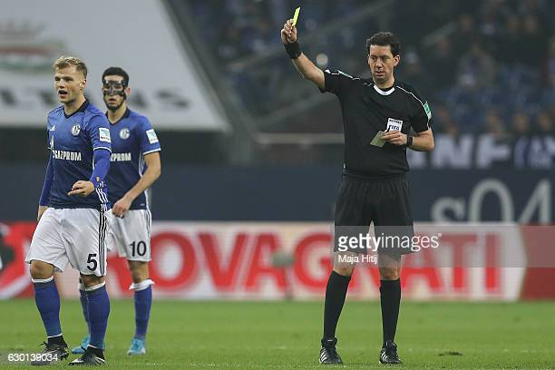 Johannes Geis of Schalke is snown a yellow card by referee Manuel Graefe during the Bundesliga match between FC Schalke 04 and SC Freiburg at...