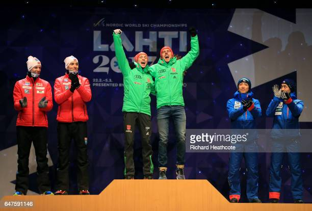 Johannes Rydzek and Eric Frenzel of Germany celebrate winning the gold medal with silver medallists Magnus Krog and Magnus Hovdal Moan of Norway and...