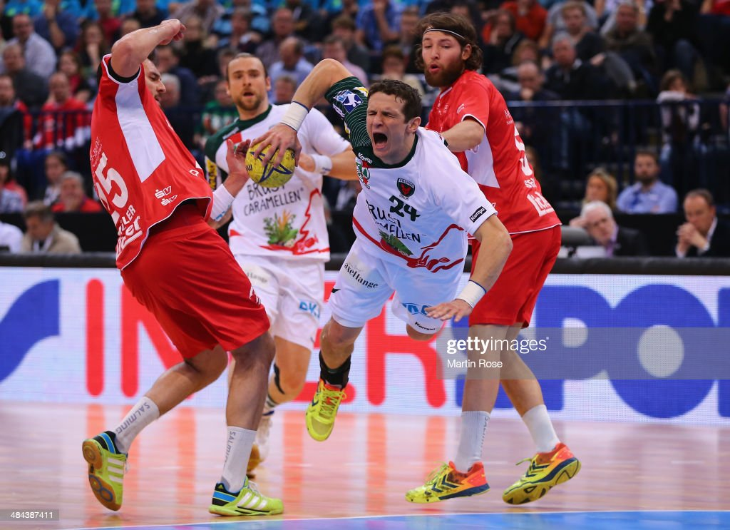 Johannes Sellin (R) of Melsungen challenges for the ball with <a gi-track='captionPersonalityLinkClicked' href=/galleries/search?phrase=Bartlomiej+Jaszka&family=editorial&specificpeople=4838990 ng-click='$event.stopPropagation()'>Bartlomiej Jaszka</a> (C) of Berlin during the DHB Pokal handball semi final match between MT Melsungen and Fuechse Berlin at O2 World on April 12, 2014 in Hamburg, Germany.