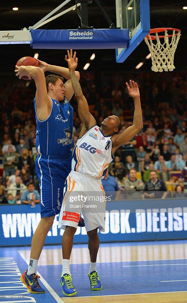 Johannes Voigtmann of Frankfurt challenges for the ball with Darius Adams of Bremerhaven during the BEKO Bundesliga basketball game between Eisbaeren...