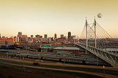 nelson mandela bridge with the johannesburg skyline in the background and moon rising