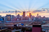 Johannesburg city sunrise panorama, with the sun rising between telkom tower and ponte city the prominent skyline skyscrapers in Johannesburg. Nelson Mandela bridge seen in the forefront and Park stat