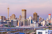 Johannesburg cityscape with at sunset, showing the Nelson Mandela Bridge. Braamfontein suburb and the railway line leading to Park Station with eight lanes of trains. The iconic telkom communication t