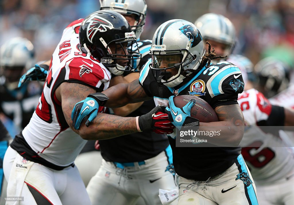 John Abraham #55 of the Atlanta Falcons tries to tackle DeAngelo Williams #34 of the Carolina Panthers during their game at Bank of America Stadium on December 9, 2012 in Charlotte, North Carolina.