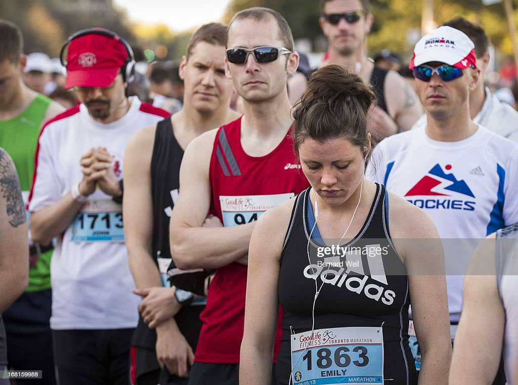 John Agellon, of Toronto (far left, red cap), Emily Rudow, of Toronto (1863) and other unidentified runners pray and bow their heads during a moment of silence to remember those who were killed and injured in the Boston Marathon, prior to the start of the Toronto Marathon. Many of the competitors wore t-shirts with 'Boston we run with you' printed on it.