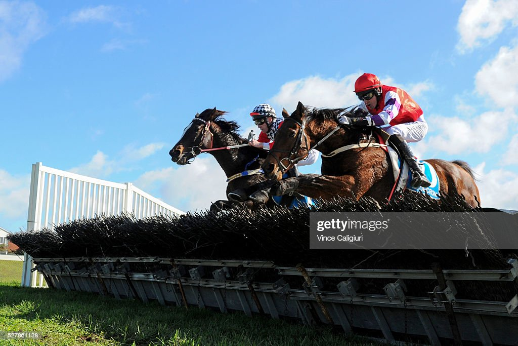 John Allen riding Waxing (L) jumps the last hurdle along side Shane Jackson riding Saddle The Stars before winning Race 1,the Decron Maiden Hurdle during Brierly Day at Warrnambool Race Club on May 4, 2016 in Warrnambool, Australia.