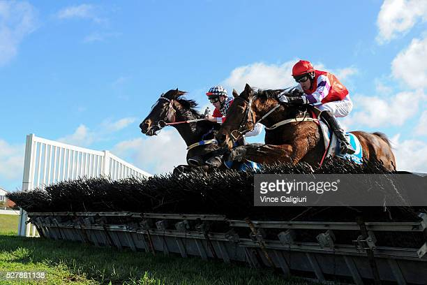 John Allen riding Waxing jumps the last hurdle along side Shane Jackson riding Saddle The Stars before winning Race 1the Decron Maiden Hurdle during...