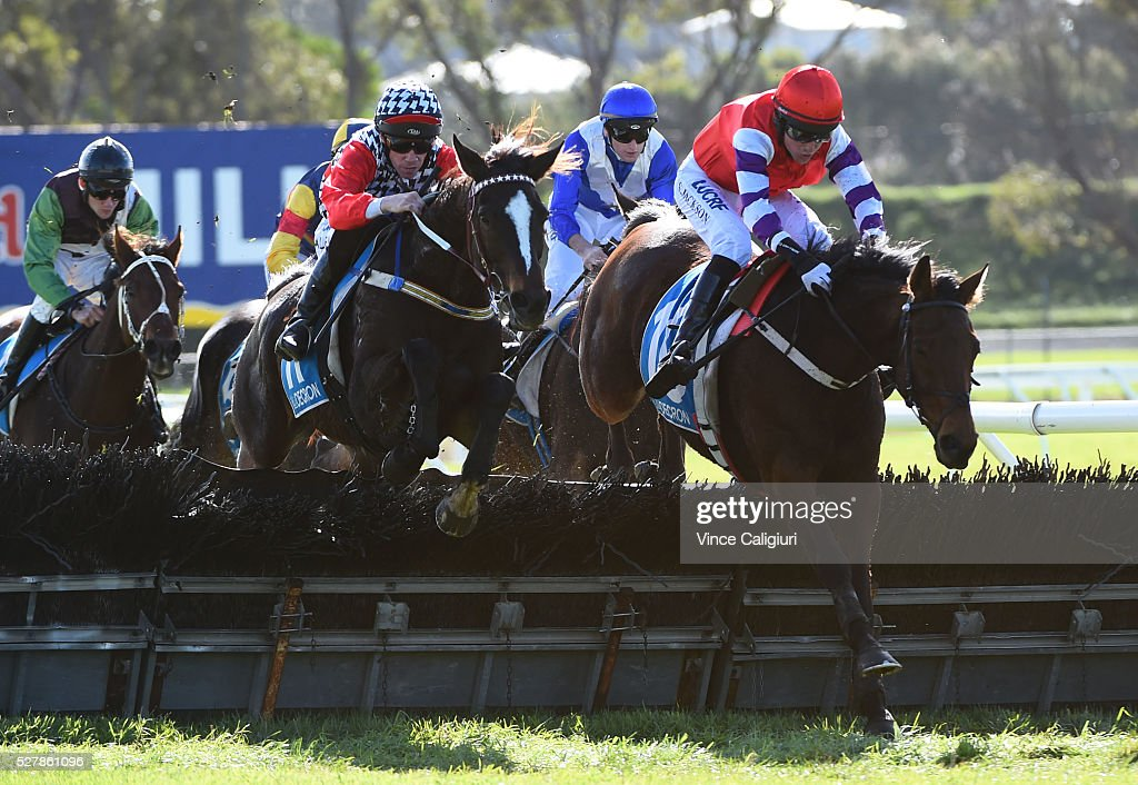John Allen riding Waxing (L) jumps the last hurdle alongside Shane Jackson riding Saddle The Stars before winning Race 1,the Decron Maiden Hurdle during Brierly Day at Warrnambool Race Club on May 4, 2016 in Warrnambool, Australia.