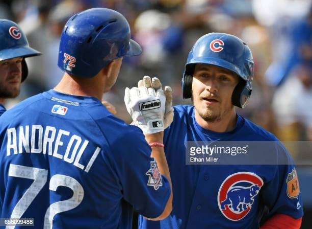 John Andreoli of the Chicago Cubs highfives teammate Bijan Rademacher at home plate after he hit a grand slam home run in the sixth inning of an...