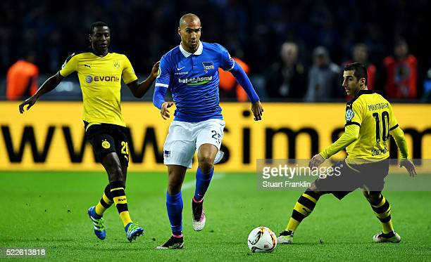 John Anthony Brooks of Berlin is challenged by Adrian Ramos and Henrikh Mkhitaryan of Dortmund during the DFB Cup semi final match between Hertha BSC...