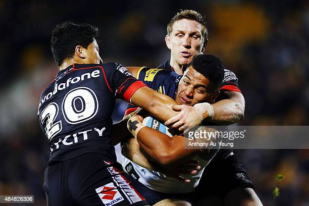 John Asiata of the Cowboys charges against Mason Lino and Ryan Hoffman of the Warriors during the round 24 NRL match between the New Zealand Warriors...