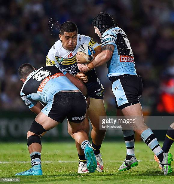 John Asiata of the Cowboys is tackled by Michael Ennis and Chris Heighington of the Sharks during the Second NRL Semi Final match between the North...