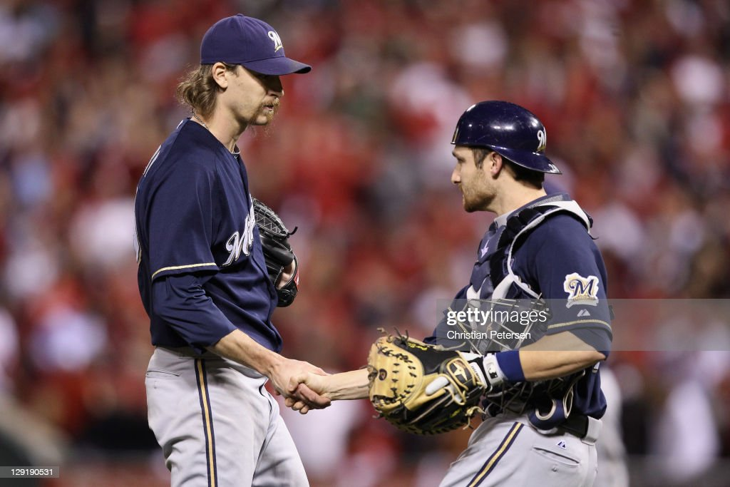 John Axford #59 and Jonathan Lucroy #20 of the Milwaukee Brewers celebrate after they won 4-2 against the St. Louis Cardinals during Game 4 of the National League Championship Series at Busch Stadium on October 13, 2011 in St. Louis, Missouri.