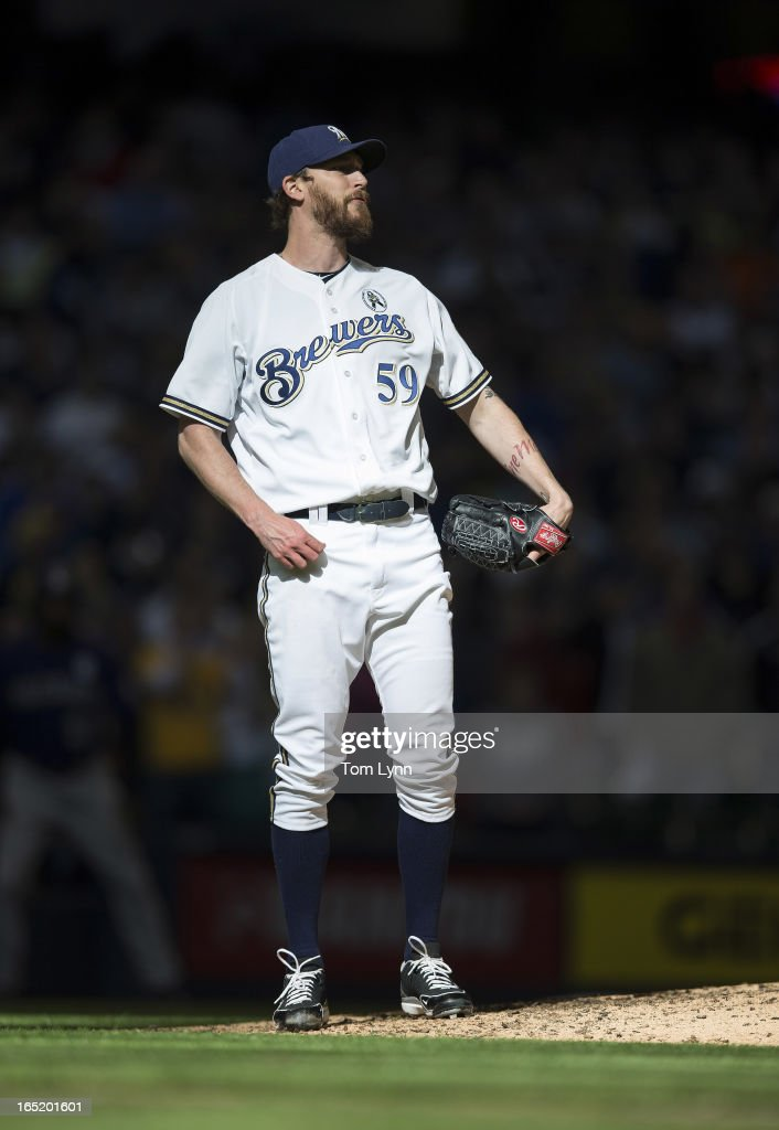John Axford #59 of the Milwaukee Brewers watches as Dexter Fowler #24 of the Colorado Rockies hits a solo home run in the ninth inning on opening day at Miller Park on April 1, 2013 in Milwaukee, Wisconsin. The Milwaukee Brewers defeated the Colorado Rockier 5-4.