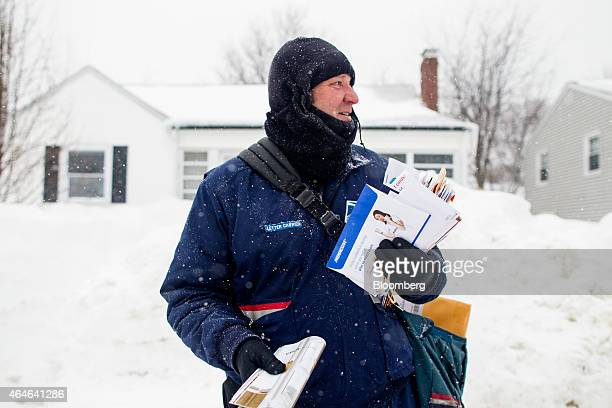 John Bachman a letter carrier for the US Postal Service checks for traffic before crossing the street in Hull Massachusetts US on Saturday Feb 21...