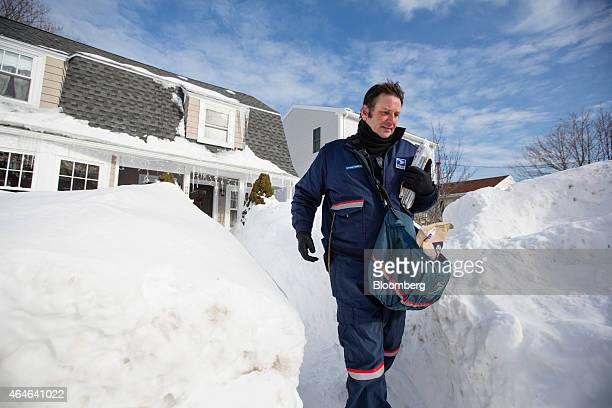 John Bachman a letter carrier for the US Postal Service walks between high snow banks after delivering mail to a house in Hull Massachusetts US on...