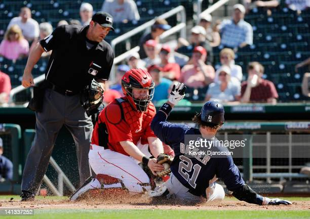 John Baker of the San Diego Padres scores a run on a double by teammate Rymer Liriano as catcher Ryan Hanigan of the Cincinnati Reds puts on the late...