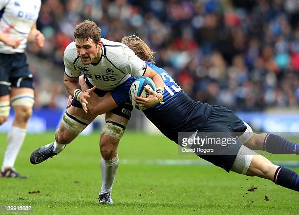 John Barclay of Scotland is tackled by Aurelien Rougerie of France during the RBS Six Nations match between Scotland and France at Murrayfield...