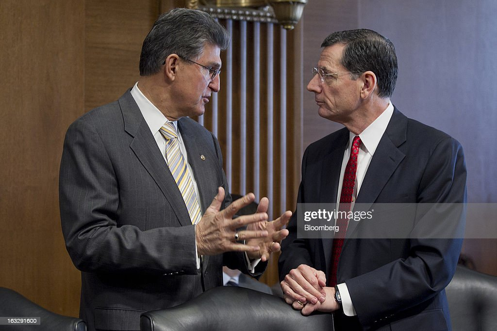John Barrasso, a Republican from Wyoming, right, talks to Joseph 'Joe' Manchin, a Democrat from West Virginia, at a Senate Energy and Natural Resources Committee confirmation hearing for Sally Jewell, president and chief executive officer of Recreational Equipment Inc. (REI) and nominee for U.S. Interior secretary, not pictured, in Washington, D.C., U.S., on Thursday, March 7, 2013. Jewell disclosed she owns shares in companies such as ConocoPhillips and Exxon Mobil Corp., which hold drilling leases managed by the Interior Department. Photographer: Andrew Harrer/Bloomberg via Getty Images