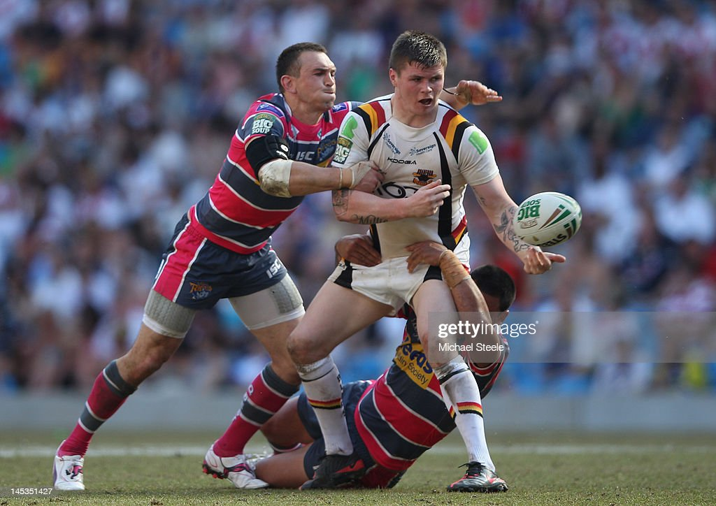 John Bateman (R) of Bradford Bulls feeds the ball as Kevin Sinfield (L) and Weller Hauraki (R) of Leeds Rhinos challenge during the Stobart Super League 'Magic Weekend' match between Bradford Bulls and Leeds Rhinos at the Etihad Stadium on May 27, 2012 in Manchester, England.