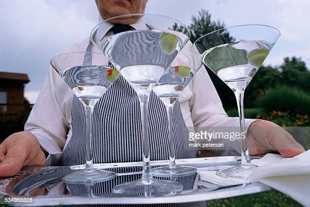 John Besteley the butler for motivational speaker and author Joe Kita carries a tray of martini glasses outside