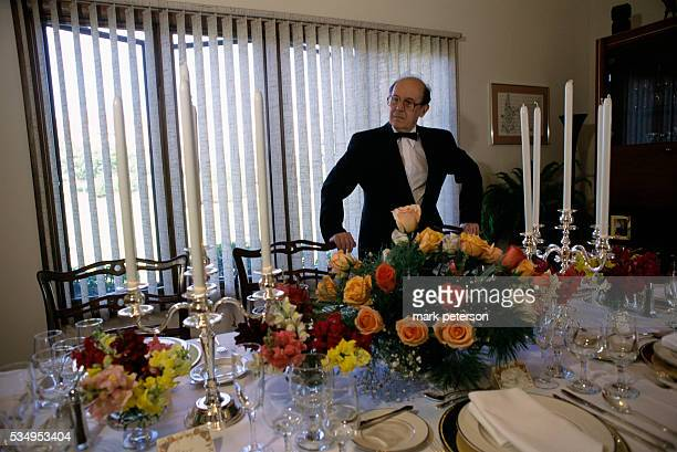 John Besteley the butler for motivational speaker and author Joe Kita arranges the dinner service in the dining room