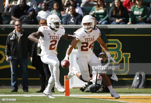 John Bonney and Kris Boyd of the Texas Longhorns celebrate Bonney's fumble recovery against the Baylor Bears in the second half at McLane Stadium on...