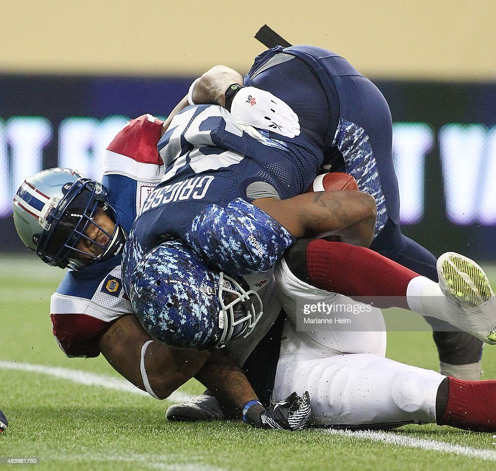 John Bowman #7 of the Montreal Alouettes gets hold of Nic Grigsby #32 of the Winnipeg Blue Bombers in second quarter action in a CFL game at Investors Group Field on August 22, 2014 in Winnipeg, Manitoba, Canada.
