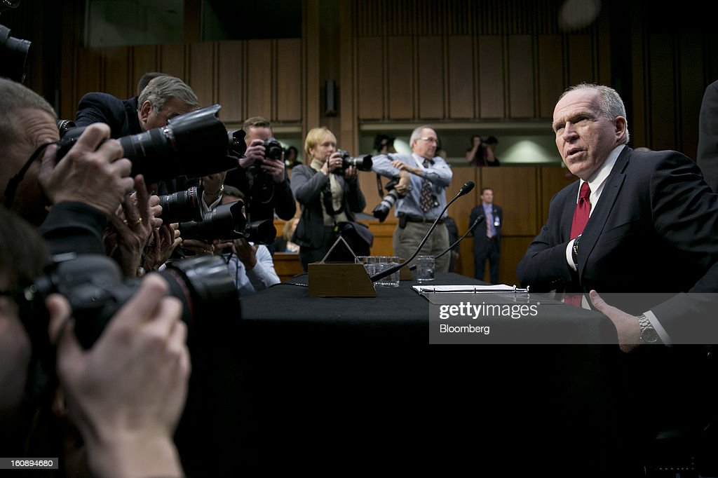 John Brennan, nominee for director of the Central Intelligence Agency (CIA) and White House chief counterterrorism adviser, right, arrives to a Senate Select Intelligence Committee hearing in Washington, D.C., U.S., on Thursday, Feb. 7, 2013. Protesters sought to set the tone at the confirmation hearing of Brennan, President Barack Obama's nominee to lead the CIA, disrupting proceedings today before Brennan even spoke. Photographer: Andrew Harrer/Bloomberg via Getty Images