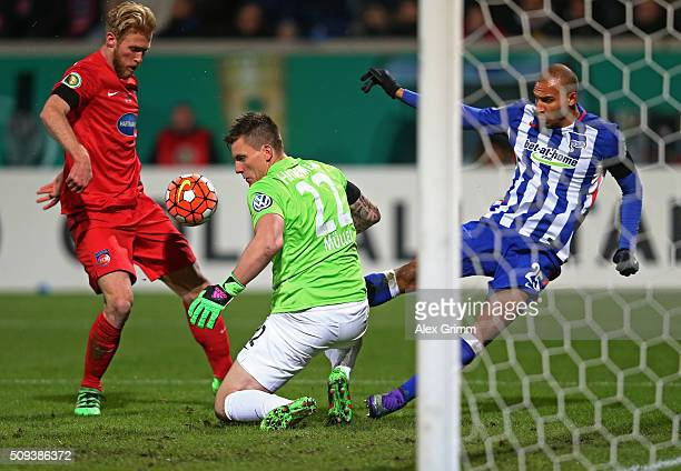 John Brooks of Hertha Berlin has a shot saved by Kevin Muller of 1FC Heidenheim during the DFB Cup quarter final match between 1 FC Heidenheim and...