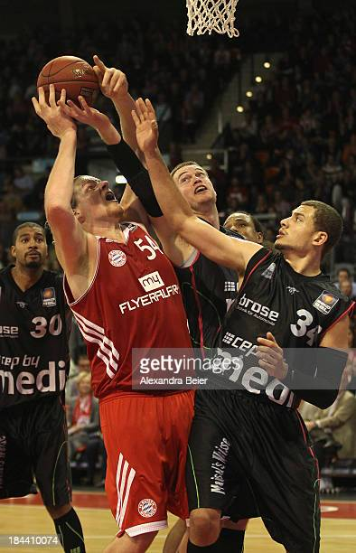 John Bryant of Bayern Muenchen fights for the ball with Kyle Weems and Brian Qvale of medi Bayreuth during the Basketball Bundesliga match between FC...