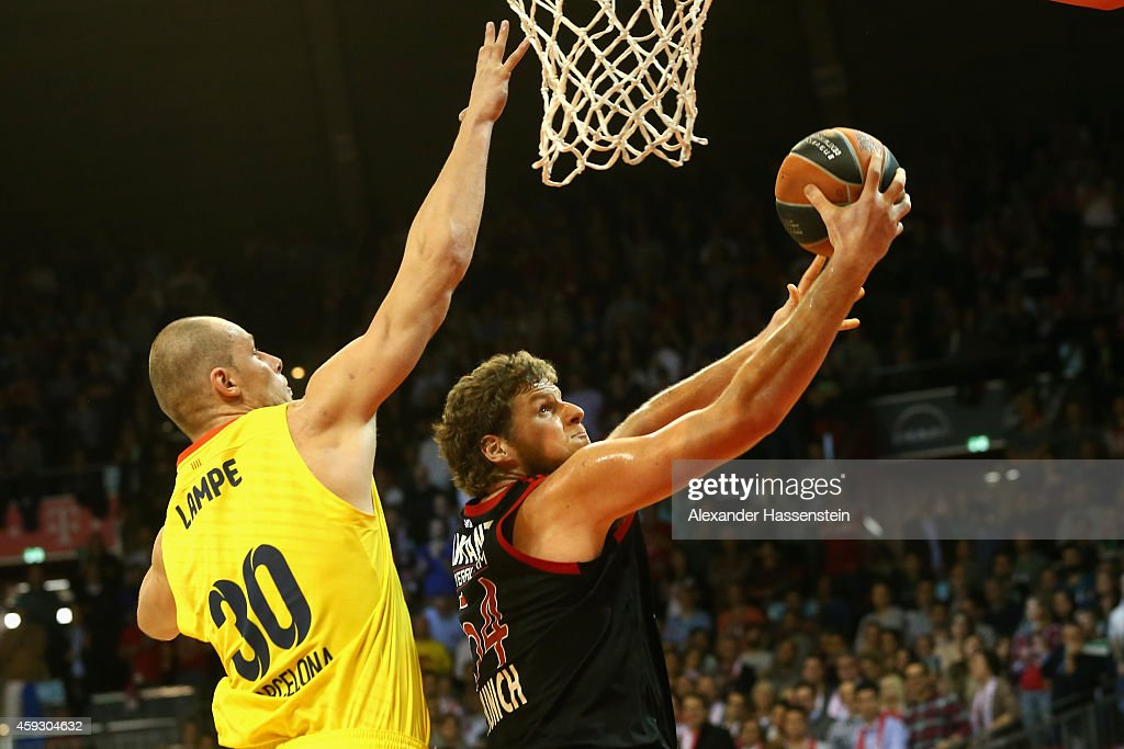 John Bryant of Bayern Muenchen iscores a point against Maciej Lampe of Barcelona during the Euroleague Basketball match between FC Bayern Munich and...