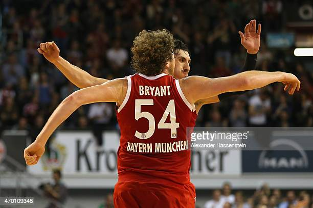John Bryant of Muenchen celebrates scoring a point with his team mate Nihad Djedovic during the Beko Basketball Bundesliga match between FC Bayern...