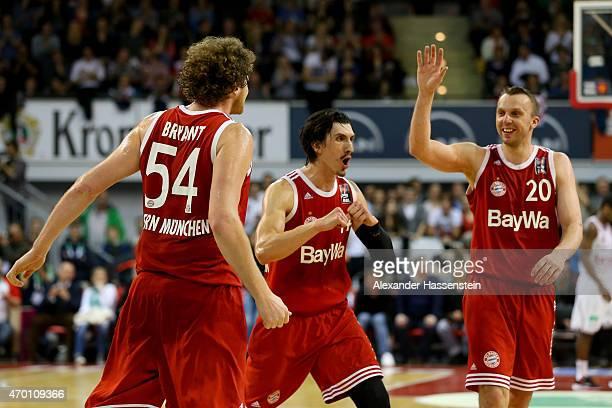 John Bryant of Muenchen celebrates scoring a point with his team mates Nihad Djedovic and Dusko Savanovic during the Beko Basketball Bundesliga match...