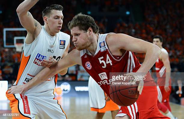 John Bryant of Muenchen is challenged by Daniel Theis of Ulm during the Beko BBL Top Four 2014 semifinal match between FC Bayern Muenchen and...