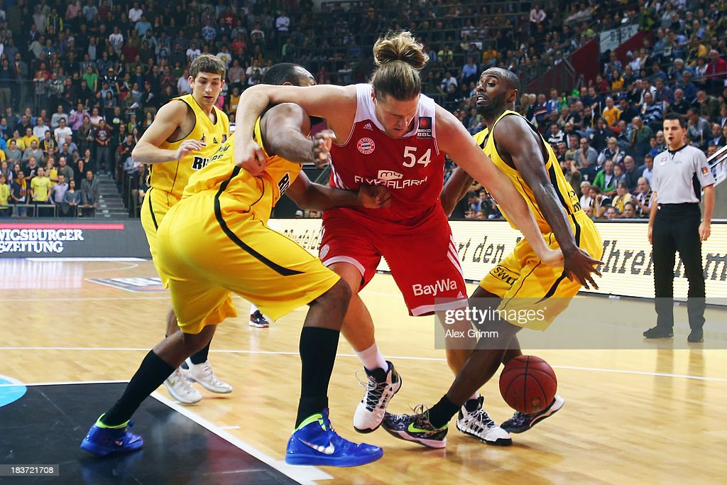 John Bryant (C) of Muenchen is challenged by Keaton Grant (R) and Gregory Echenique of Ludwigsburg during the BBL match between MHP RIESEN Ludwigsburg and Bayern Muenchen at MHPArena on October 9, 2013 in Ludwigsburg, Germany.