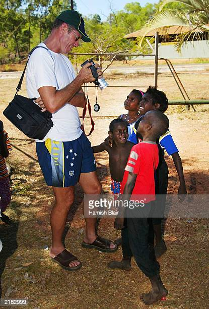 John Buchanan of Australia meets some locals on July 22 2003 during a team visit to an Aboriginal settlement on Melville Island off the coast of...