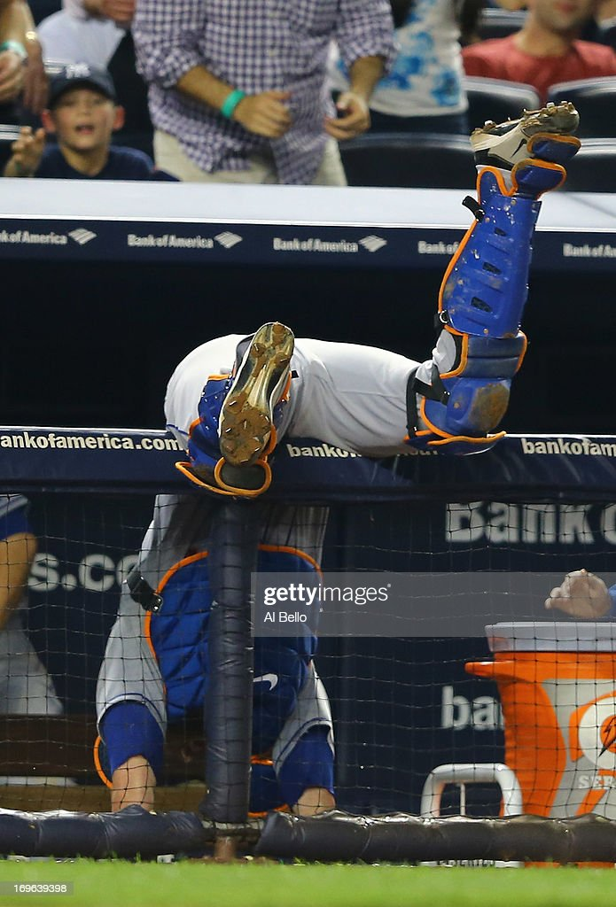<a gi-track='captionPersonalityLinkClicked' href=/galleries/search?phrase=John+Buck&family=editorial&specificpeople=213730 ng-click='$event.stopPropagation()'>John Buck</a> #44 of the New York Mets flips over the dugout trying to catch a foul ball hit by Ichiro Suzuki #31 of the New York Yankees during their game on May 29, 2013 at Yankee Stadium in the Bronx borough of New York City