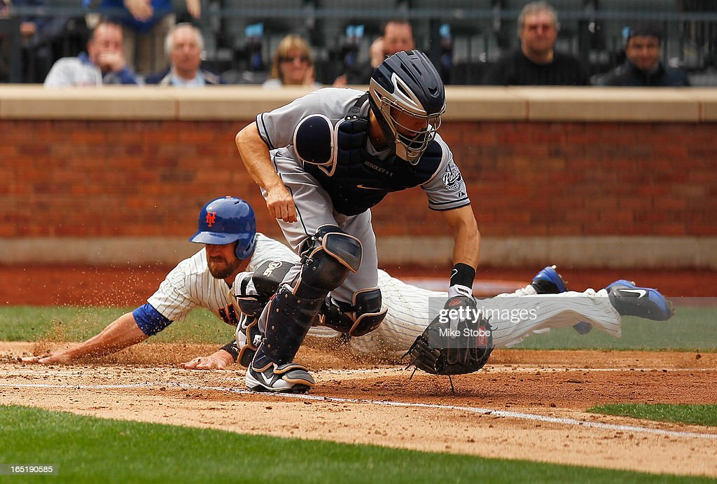 <a gi-track='captionPersonalityLinkClicked' href=/galleries/search?phrase=John+Buck&family=editorial&specificpeople=213730 ng-click='$event.stopPropagation()'>John Buck</a> #44 of the New York Mets slides in safely ahead of the tag of <a gi-track='captionPersonalityLinkClicked' href=/galleries/search?phrase=Nick+Hundley&family=editorial&specificpeople=4175399 ng-click='$event.stopPropagation()'>Nick Hundley</a> #4 of the San Diego Padres on a Ruben Tejada RBI double in the second inning on opening day at Citi Field on April 1, 2013 in the Flushing neighborhood of the Queens borough of New York City.
