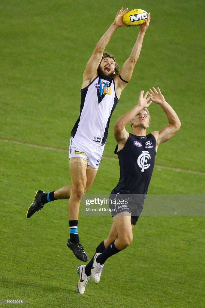 John Butcher marks the ball against Matthew Watson of the Blues during the round one AFL match between the Carlton Blues v Port Adelaide Power at Etihad Stadium on March 16, 2014 in Melbourne, Australia.