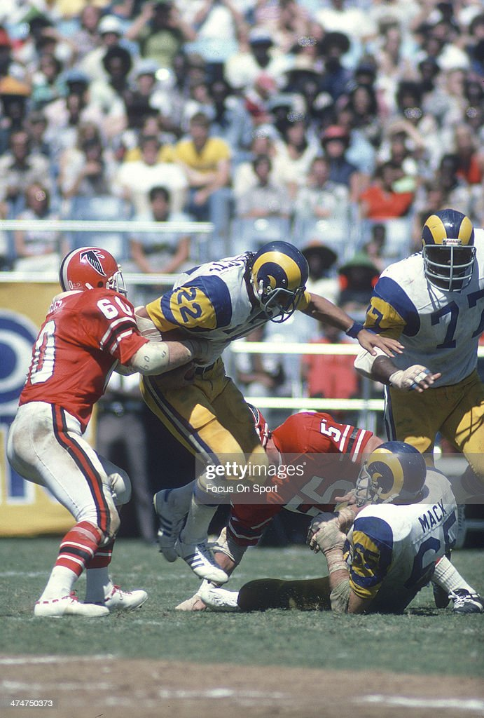 John Cappelletti #22 of the Los Angeles Rams gets grabbed by <a gi-track='captionPersonalityLinkClicked' href=/galleries/search?phrase=Tommy+Nobis&family=editorial&specificpeople=993224 ng-click='$event.stopPropagation()'>Tommy Nobis</a> #60 of the Atlanta Falcons during an NFL football game at Atlanta-Fulton County Stadium September 12, 1976 in Atlanta, Georgia. Cappelletti played for the Rams from 1974-78.