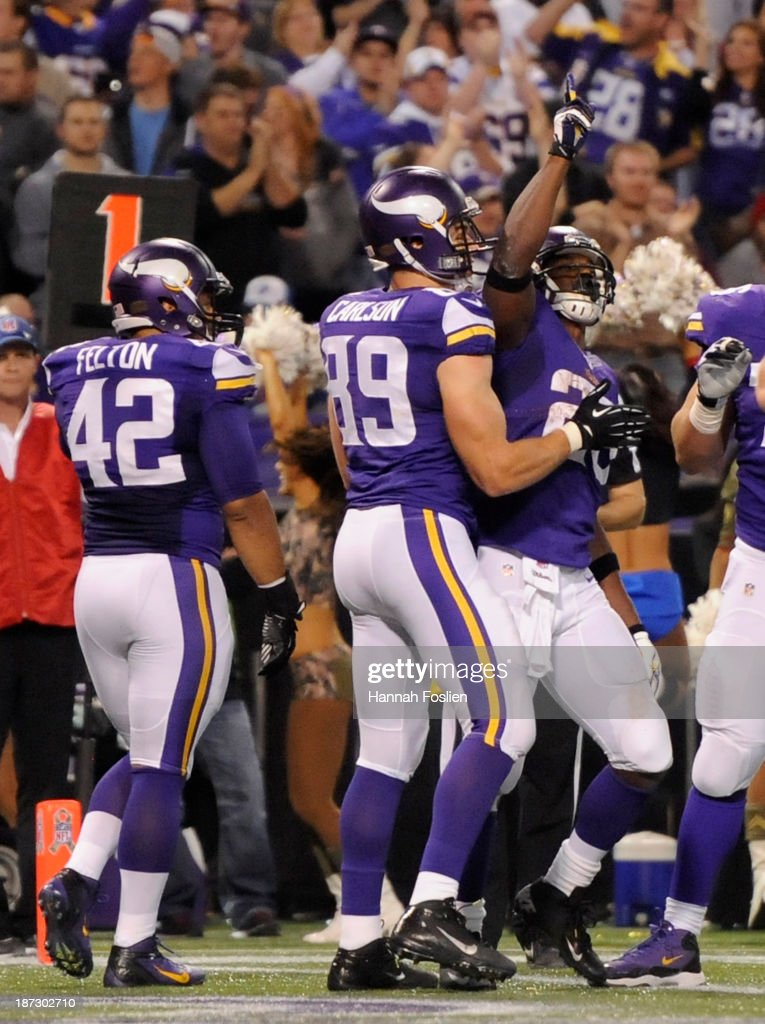 John Carlson #89 and Adrian Peterson #28 of the Minnesota Vikings celebrate a touchdown against the Washington Redskins by Peterson during the third quarter of the game on November 7, 2013 at Mall of America Field at the Hubert H. Humphrey Metrodome in Minneapolis, Minnesota.