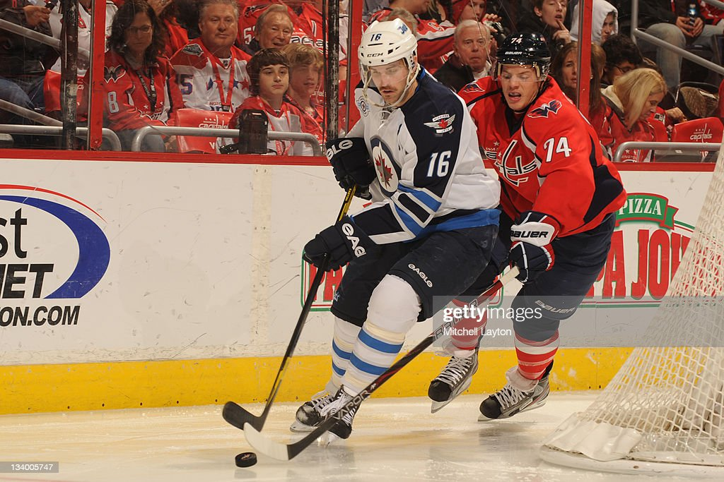 John Carlson #74 of the Washington Capitals and <a gi-track='captionPersonalityLinkClicked' href=/galleries/search?phrase=Andrew+Ladd&family=editorial&specificpeople=228452 ng-click='$event.stopPropagation()'>Andrew Ladd</a> #16 of the Winnipeg jets fight for the puck during a NHL hockey game on November 23, 2011 at the Verizon Center in Washington, DC.