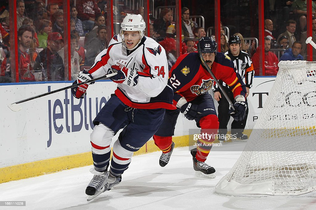 John Carlson #74 of the Washington Capitals and George Parros #22 of the Florida Panthers chase a loose puck into the corner at the BB&T Center on April 6, 2013 in Sunrise, Florida. The Capitals defeated the Panthers 4-3.