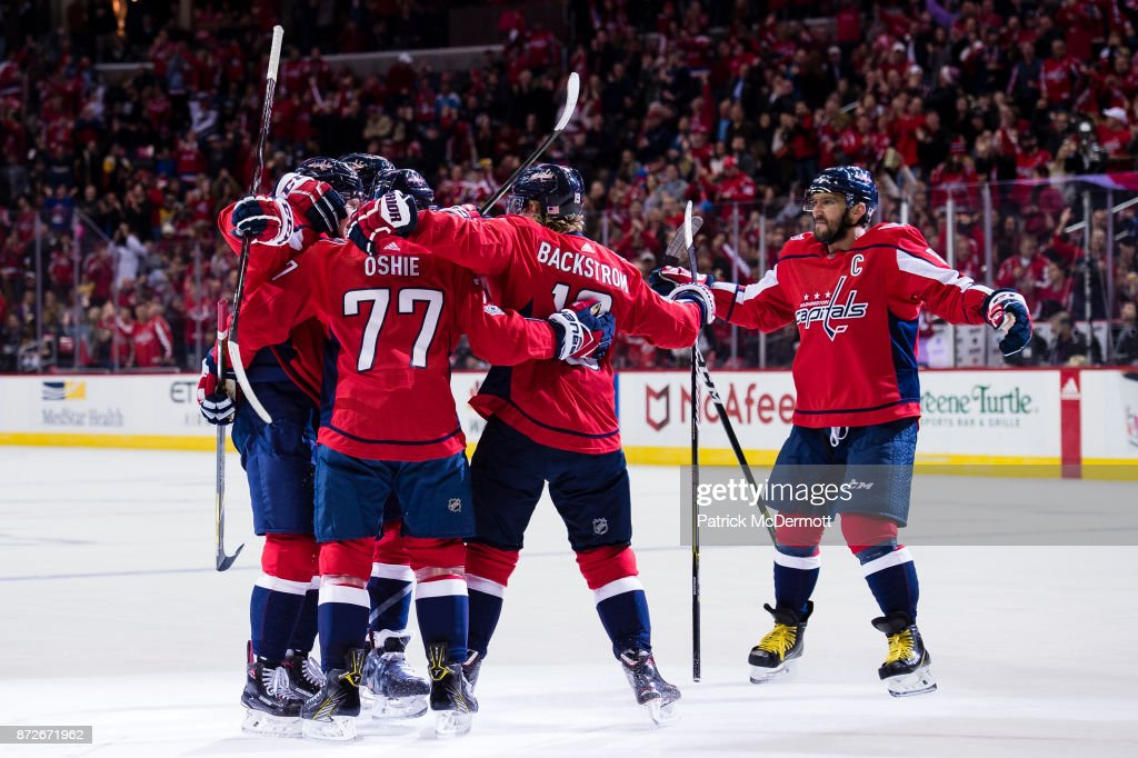 John Carlson #74 of the Washington Capitals celebrates with his teammates after scoring a first period goal against the Pittsburgh Penguins at Capital One Arena on November 10, 2017 in Washington, DC.